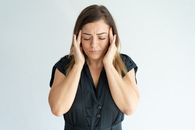 疲れを強調した若い女性が黒いドレスで頭痛を感じ、寺院をマッサージします。