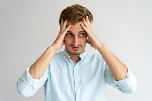 Расстроенный путаный парень чувствует себя виноватым. молодой кавказский красивый мужчина с головой
