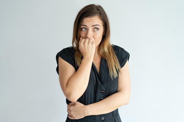 Обеспокоенная молодая женщина, кусая ногти, с беспокойством.