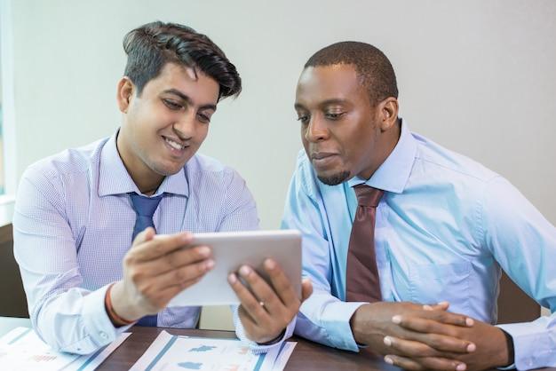 新しいアプリをテストする陽気なビジネス同僚