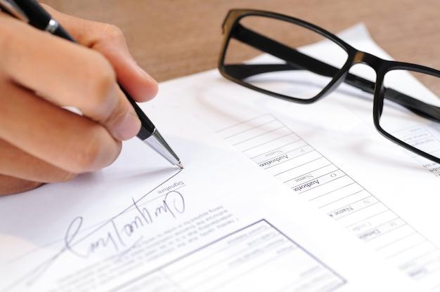 文書に署名する人のクローズアップ