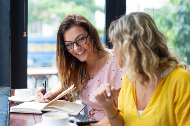 コーヒーを飲み、カフェで働く幸せな女性