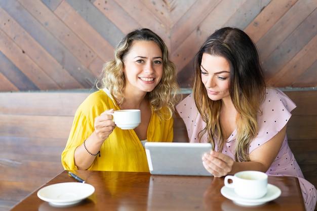 カフェでタブレットコンピュータとコーヒーを飲むかなりの女性