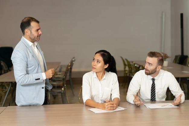 Серьезные деловые люди работают и обсуждают проблемы на столе