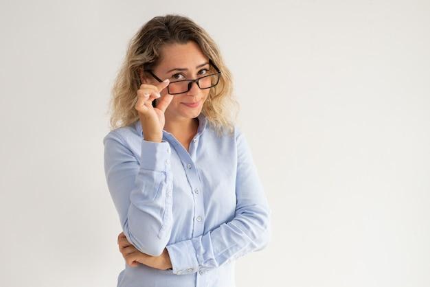 彼女の眼鏡を見下ろす深刻なおしゃれなビジネスレディ