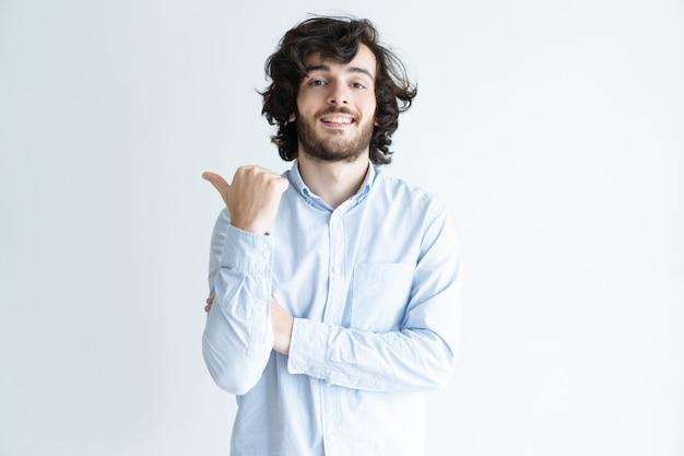 Улыбающийся бородатый молодой человек, указывая пальцем в сторону