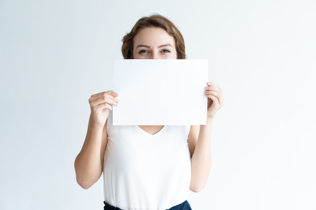 Улыбаясь довольно молодая женщина, прячась за чистый лист бумаги