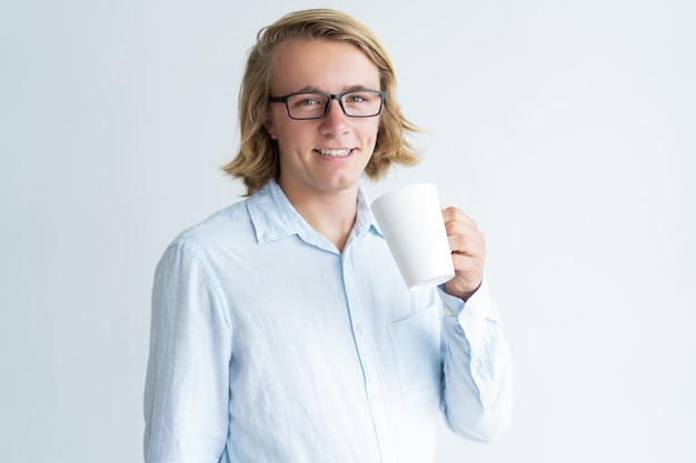 マグカップをしてカメラを見ている笑顔の若い男
