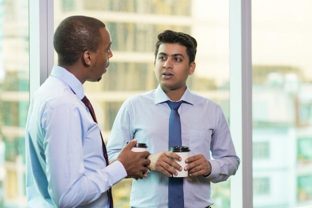 Молодые деловые люди пьют кофе и болтают во время перерыва
