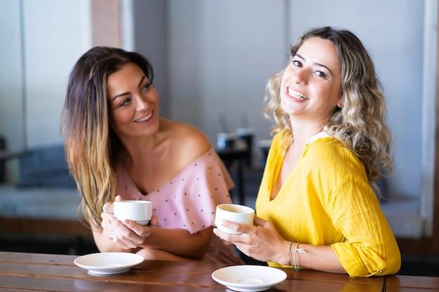 若い女性が笑い、コーヒーを飲む、カフェ