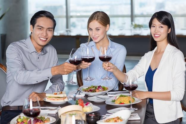 レストランでワインを飲むハッピービジネス旅行者