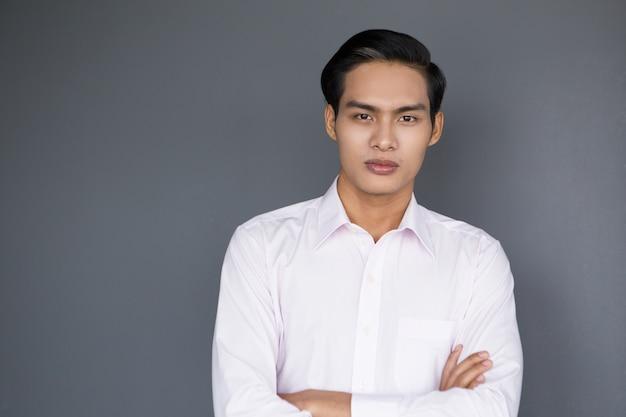 クロスアームの深刻な若いアジアのビジネスマン