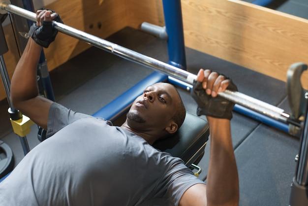 Черный человек, лежащий и поднимающий штангу в тренажерном зале