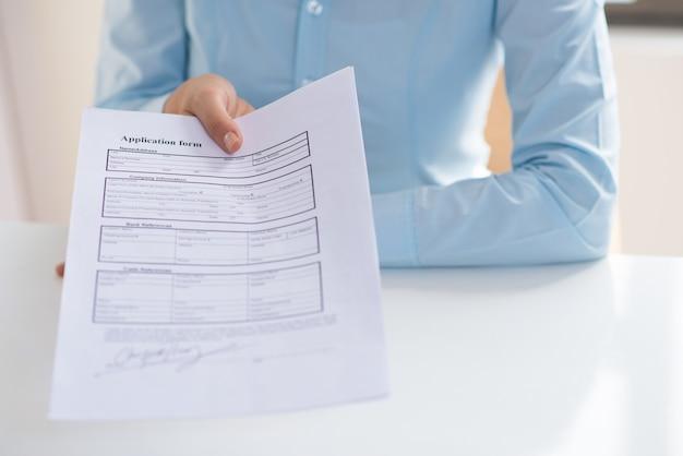 Макрофотография лица, дающего подписанную форму заявки для просмотра
