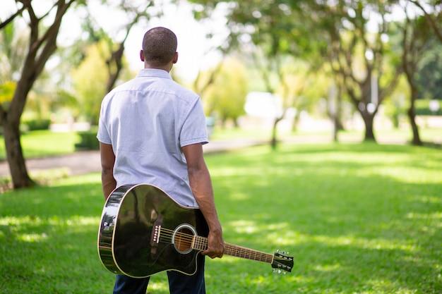 Черный человек, несущий гитару в парке