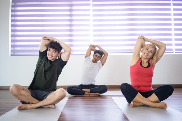 ヨガのクラスで腕を伸ばしているポジティブな人々