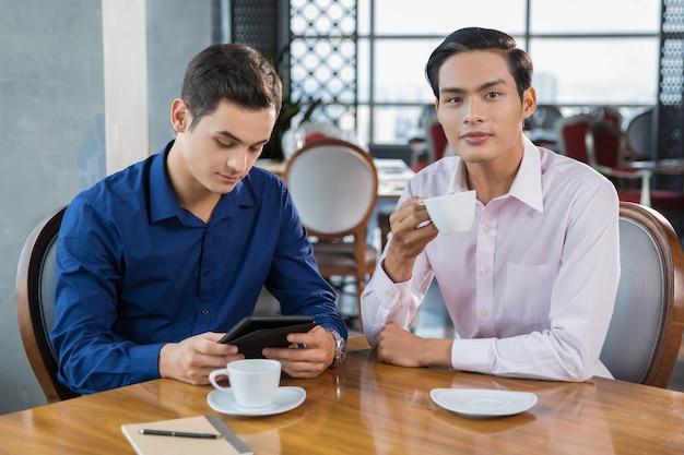 二つのビジネスマンの作業と飲むコーヒー