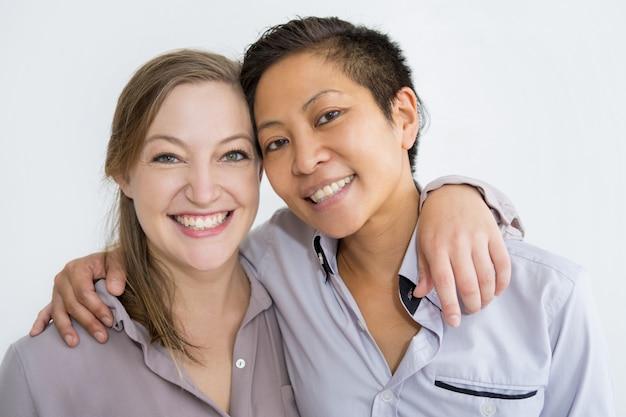 抱きしめるとカメラでポーズを取る笑顔の女性