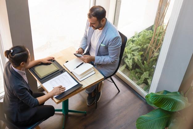 カフェでミーティングを持つ深刻なビジネスパートナーの視点から