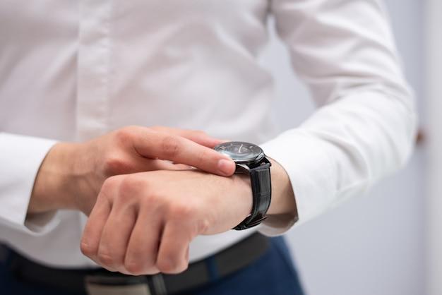 彼の近代的な腕時計を見ているビジネスマンのクローズアップ