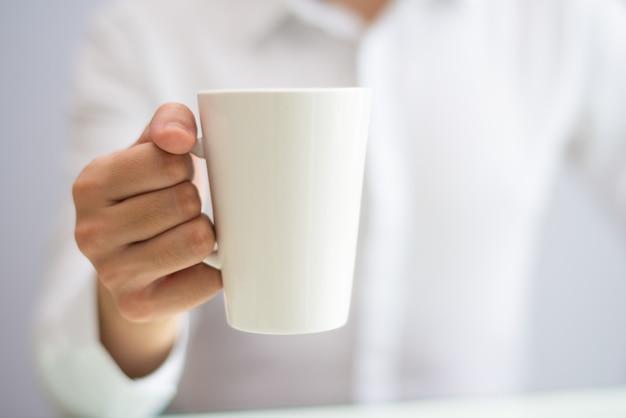 マグカップからのオフィスの従業員の飲み物のコーヒーのクローズアップ