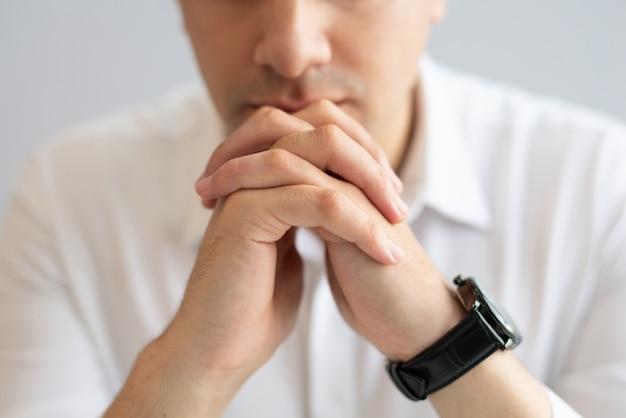 Крупным планом задумчивый молодой бизнесмен, сидя со сложенными руками