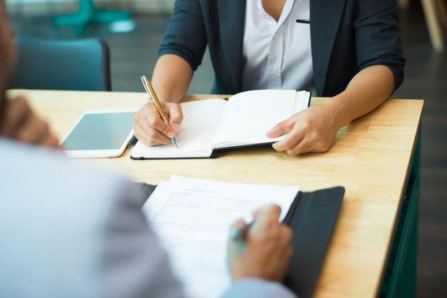 テーブルに座ってノートを書くメモの女性のクローズアップ