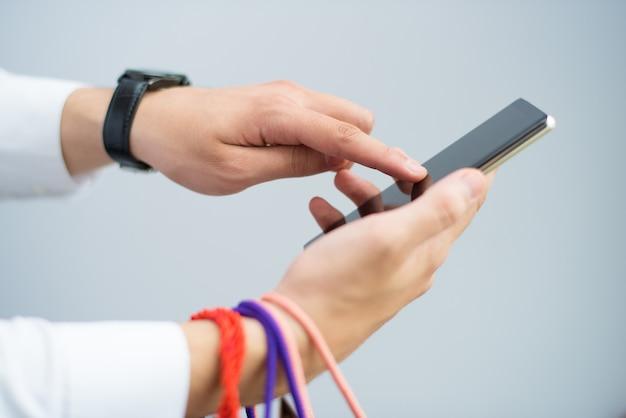 Крупным планом мужчина держит сумок и с помощью смартфона