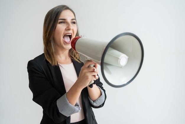 Уверенная молодая кавказская женщина кричит в сторону в мегафон