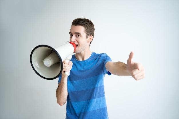 メガホンで話して、あなたを指差している興奮した男