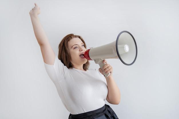幸せな若い女性が腕を上げてメガホンで叫ぶ