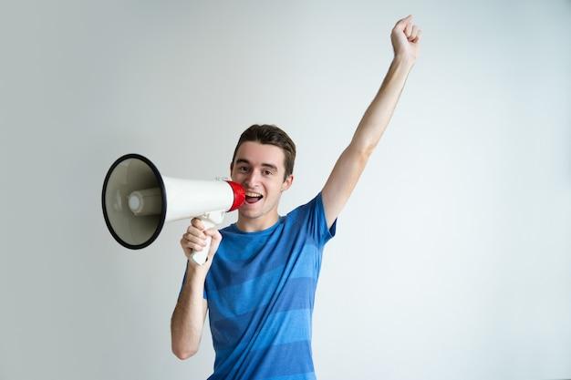 幸せな男がメガホンに話しかけ、腕を上げる