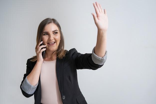 手を振って電話で幸せな若い白人の実業家