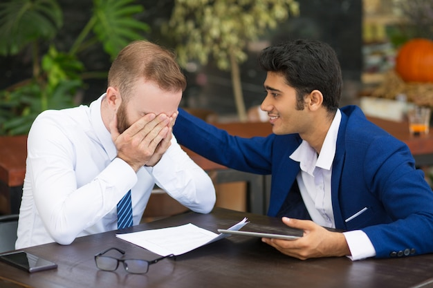 Индийский бизнесмен поддерживает коллегу и поглаживает его спину