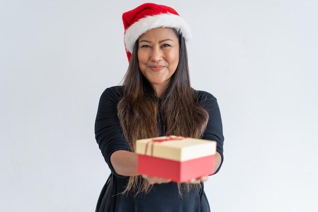 喜ばしいクリスマスの贈り物を与える女性