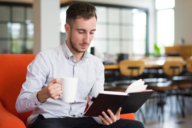 カップを持って読書をしている夢中の白人の若い男