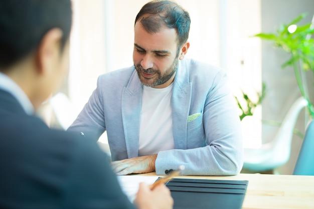 Портрет улыбающегося среднего взрослого бизнесмена сидеть и писать