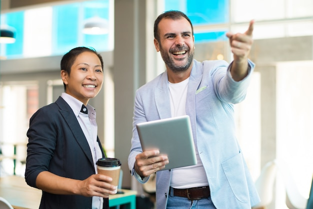 オフィスでコーヒーを飲むポジティブなラテン、アジアのマネージャー