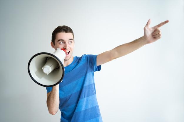 Позитивный человек говорит в мегафон и указывая в сторону
