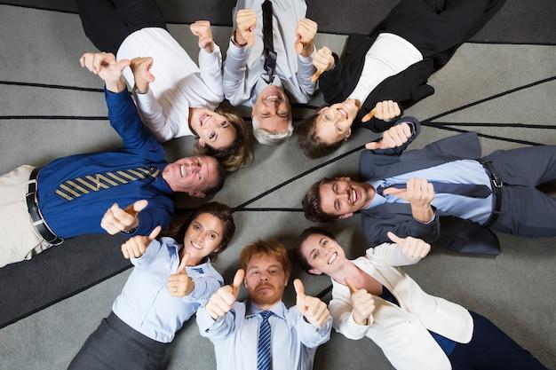 フロアに親指を表示朗らかビジネスチーム