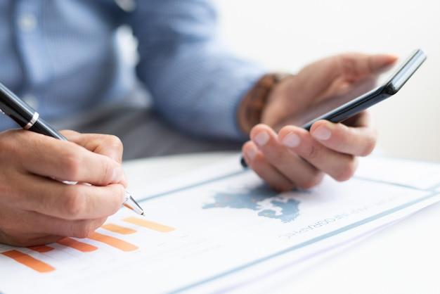 Крупным планом деловой человек, работающий с диаграммой