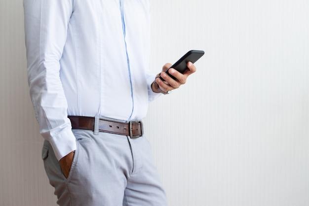 Крупным планом бизнесмена холдинг и с помощью смартфона