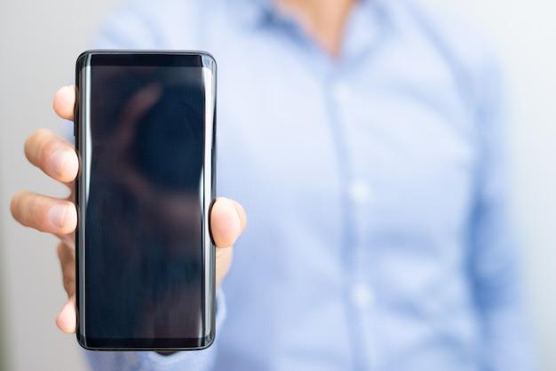 空のスマートフォンの画面を見せて男のクローズアップ