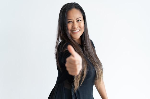 Уверенно красивая женщина среднего возраста, показывая большой палец вверх