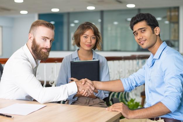 会社のリーダーと握手するインドの候補者