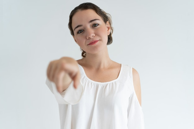 Довольная милая женщина указывая на тебя