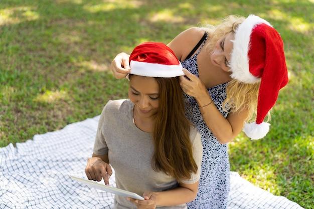 夏の公園でクリスマスの準備をしてコンテンツの若い女性