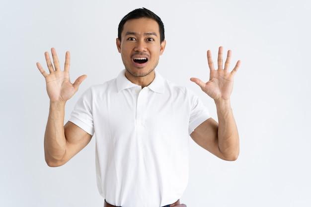 Возбужденный парень поднимает руки в шоке, удивлении или пугающем жесте