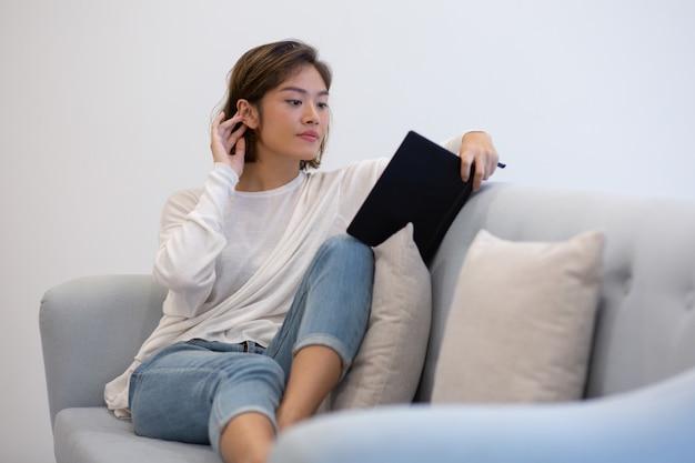 Вдохновленная азиатская девушка, читающая книгу