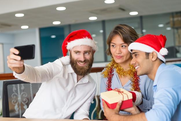 Радостная многонациональная рабочая группа наслаждается офисной рождественской вечеринкой